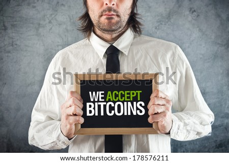 Businessman holding board with title WE ACCEPT BITCOINS as form of payment. - stock photo