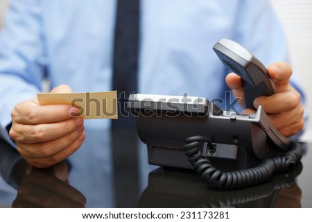 businessman holding business card and calling his client - stock photo