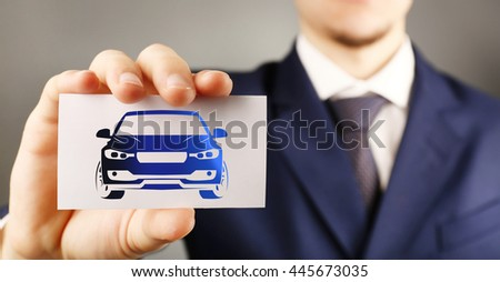 Businessman holding business card with picture of car