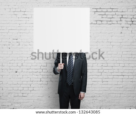 businessman holding card and brick wall - stock photo