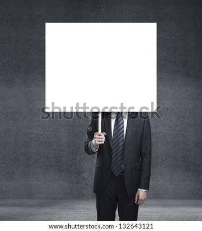 businessman holding card and concrete wall - stock photo