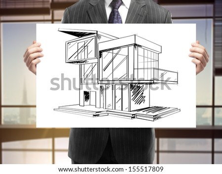 businessman holding card with house