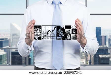 businessman holding chart and business symbol - stock photo