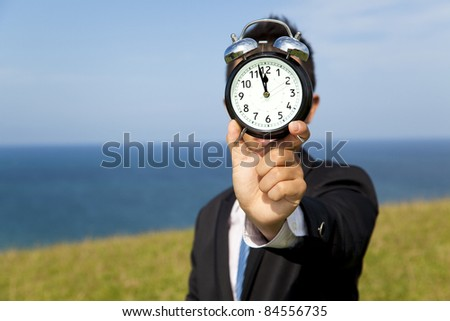 businessman holding clock and standing on the field