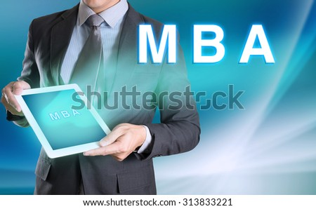 businessman holding computer tablet in hand and show MBA word - stock photo