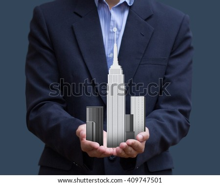 Businessman holding construction building model on hand. - stock photo