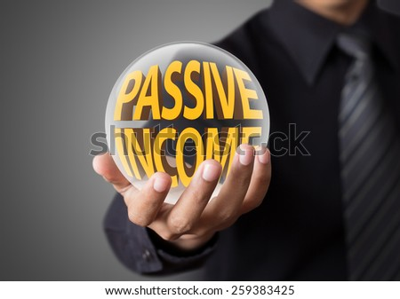 Businessman holding crystal ball with passive income concept  - stock photo