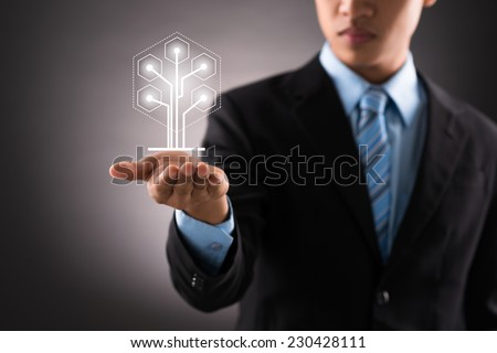 Businessman holding digital image of tree in front of him - stock photo
