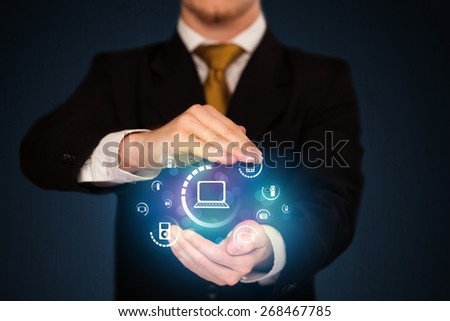 Businessman holding digital media icons - stock photo