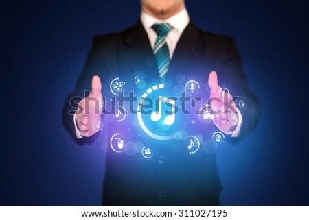 Businessman holding digital multimedia icons - stock photo