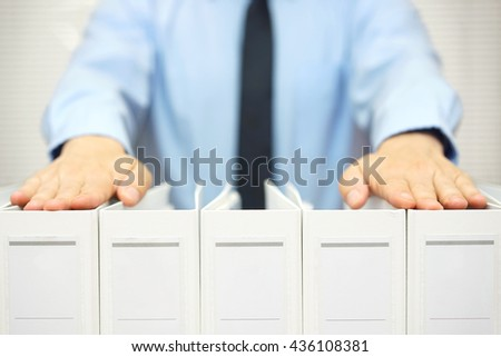 businessman holding documentation in binders, accounting & business concept - stock photo