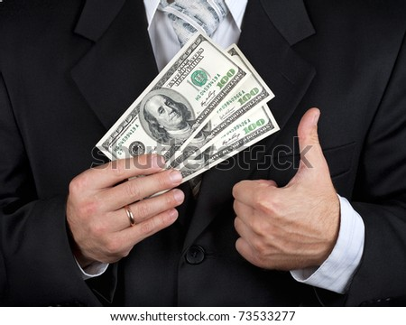 Businessman holding dollar banknotes and making his thumb up - stock photo
