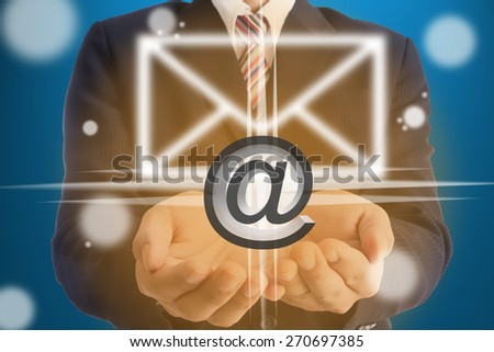Businessman holding e-mail sign for send and communication with partnership  - stock photo