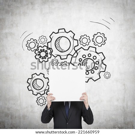Businessman holding empty banner. A concept of well organized work process - Gears sketch on the wall.