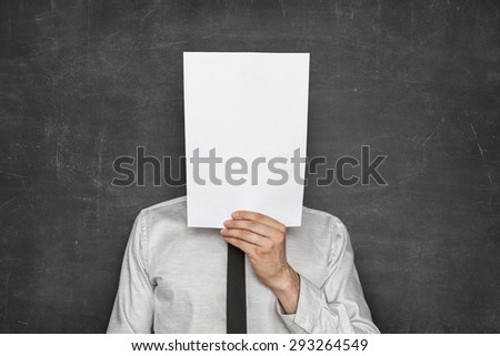Businessman holding empty paper sheet front of head on blackboard background - stock photo