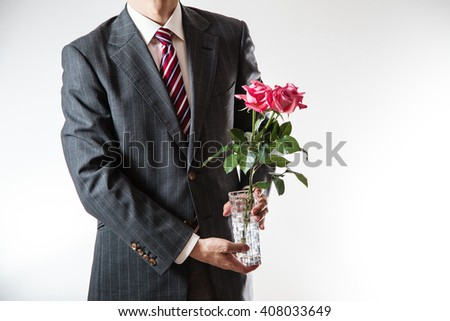 Businessman holding flowers - stock photo