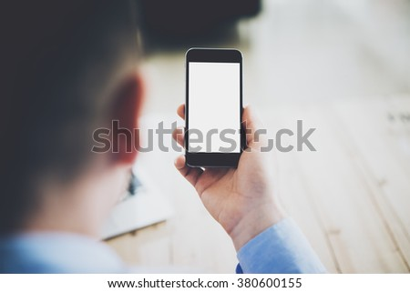 Businessman holding generic design smartphone with blank screen in hands. Ready for message. Horizontal mockup - stock photo