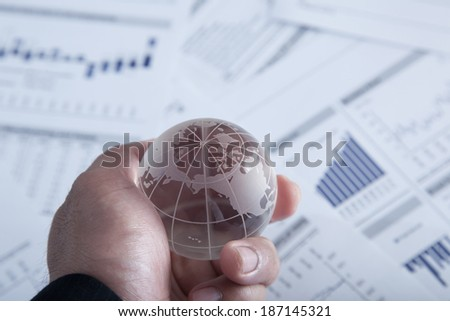 Businessman holding glass globe with chart papers. - stock photo