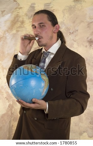 Businessman holding globe and cigar