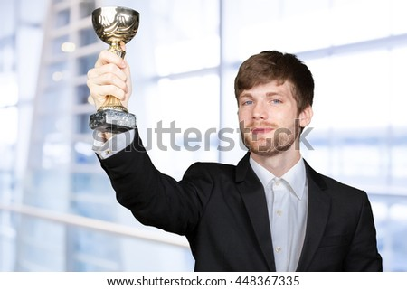Businessman holding golden cup trophy
