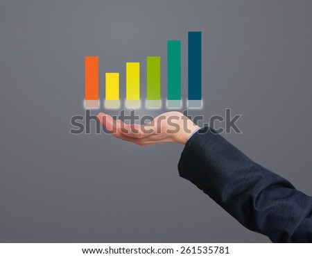 Businessman holding graph in his hand . Grey - Stock Photo