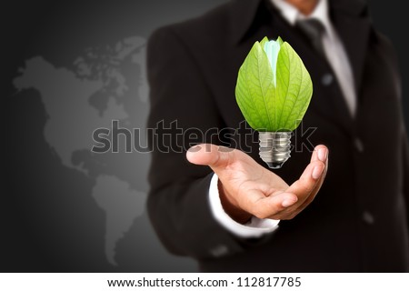 Businessman holding green light bulb, concept of saving energy - stock photo