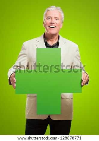 Businessman Holding Green Plus Sign against a green background - stock photo
