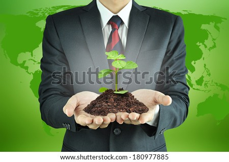 Businessman holding green sprout with soil - sustainable development & conservation concept - stock photo