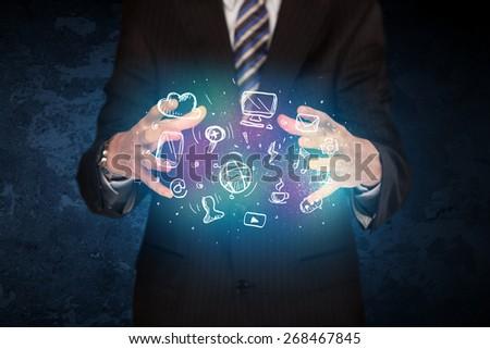 Businessman holding hand drawn media icons - stock photo
