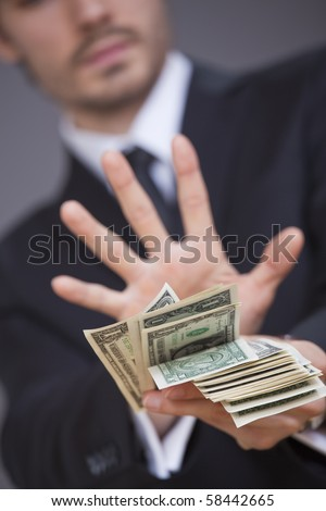businessman holding hand in front of dollars rejecting a bribe - stock photo