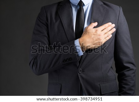 Businessman holding hand on his chest - stock photo