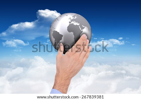 Businessman holding hand out in presentation against bright blue sky with clouds