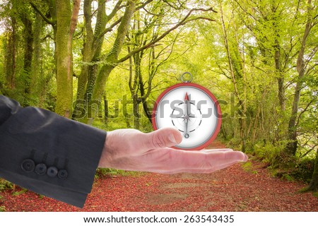 Businessman holding hand out in presentation against peaceful autumn scene in forest - stock photo