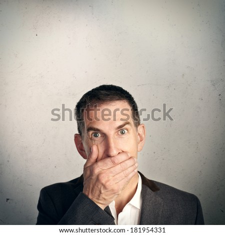 Businessman holding hand over his mouth - stock photo