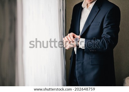 Businessman holding hand with wrist watches in pocket isolated on white - stock photo