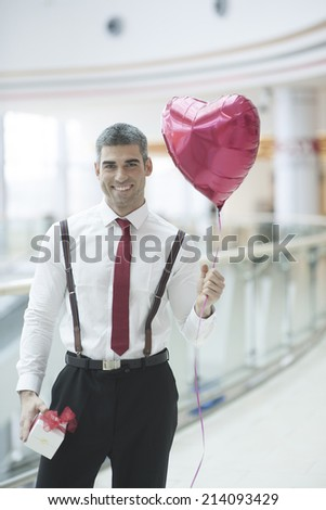 Businessman holding heart shaped balloon and present - stock photo