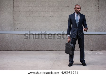 businessman holding his briefcase using smart phone in urban background  - stock photo