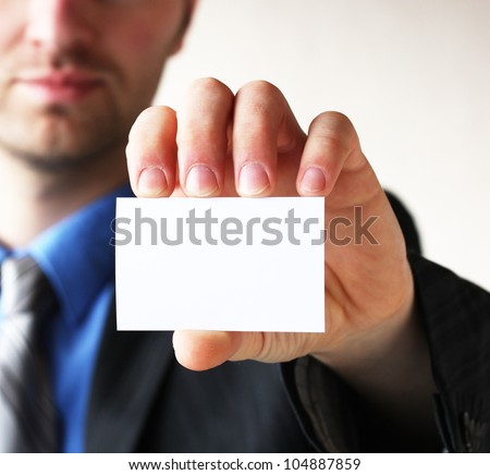 Businessman holding his business card in hand - stock photo