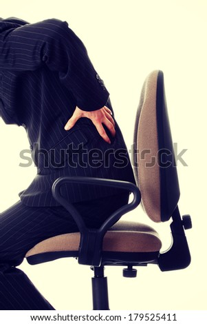 Businessman holding his hand to his aching back  - stock photo