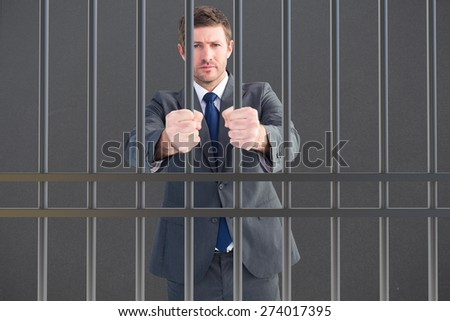 Businessman holding his hands out against grey - stock photo