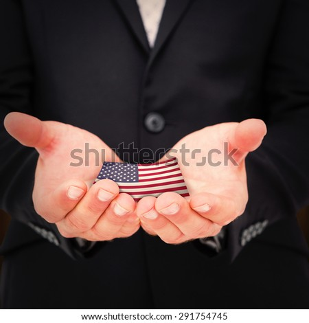 Businessman holding his hands out against rural fields - stock photo