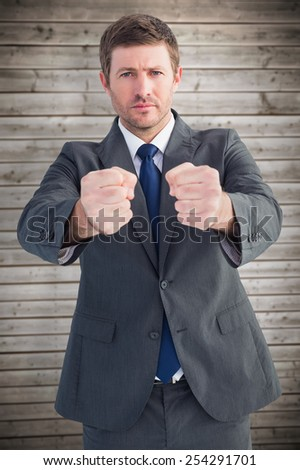 Businessman holding his hands out against wooden planks background - stock photo
