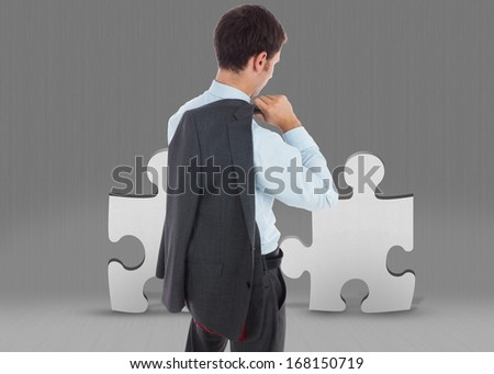 Businessman holding his jacket against grey jigsaw pieces