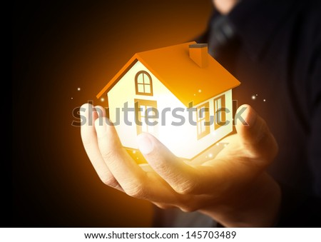 Businessman holding home model - stock photo