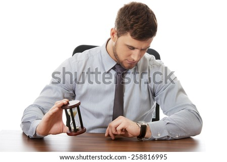 Businessman holding hourglass an checking time on his watch. - stock photo