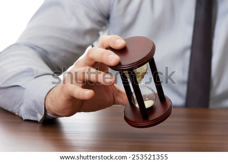 Businessman holding hourglass in the office. - stock photo