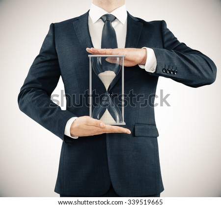 Businessman holding hourglass, time concept  - stock photo
