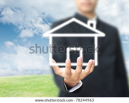 Businessman holding house - stock photo