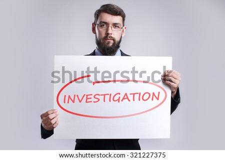 "Businessman holding in the hands white poster with handwriting red text ""investigation"". Business concept. - stock photo"