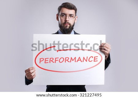 """Businessman holding in the hands white poster with handwriting red text """"Performance"""". Business, internet, technology concept. - stock photo"""